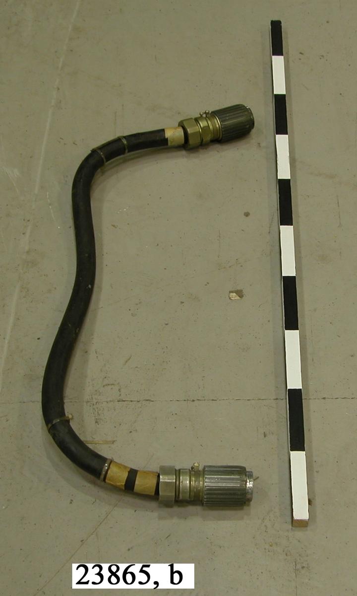 Kabel av gummi. I ändarna sitter grönlackerade kopplingsanordningar av aluminium. Kopplingarna har ytterst gängade hylsor vilka används för att låsa bakeln till instrumentet.