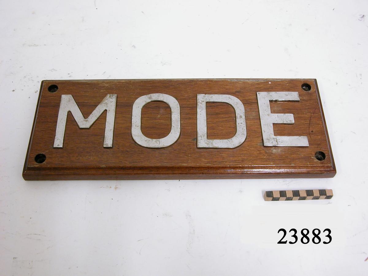 """Rektangulär, lackad träplatta med raka hörn och falsad kant. På framsidan versala bokstäver av rostfritt stål """"MODE"""" som är fastskruvade från brädans baksida. Bokstävernas höjd: 100 mm. Hål i plattans vardera hörn för uppmontering."""