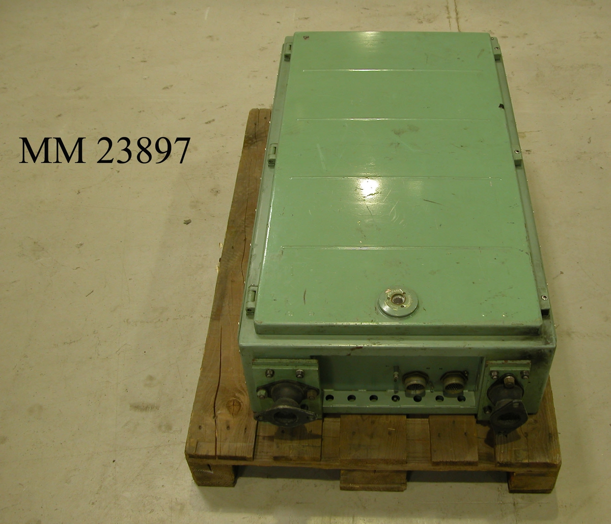 """Digitalräknare till torpedcentralinstrument (TCI) 105. Turkos- eller grönlackerat, rektangulärt instrument av metall. Framsidan utgörs av en stor lucka som går att skruva upp. Mitt på luckan (framsidan) nedtill finns ett inspektionshål märkt """"SILICAGEL"""". På nedre vänstersida finns en fläkt. Hela instrumentet är placerat på två stycken vibrationsdämpande gummifötter, undersidan av fötterna dock av metall. Upptill på framsidan av instrumentet sitter två stycken mindre metallbrickor, den ena med texten: """"9 TCI ANL 2 ENH 13 DIGITALRÄKNARE"""". Den andra med texten: """"PHILIPS TYP RF 869:32 NR 96219 STOCKHOLM SWEDEN"""". På luckans insida finns ett vitt placeringsschema för instrumentets interna komponenter, såsom minnesenheten. Avslutningsvis finns det anslutningsmöjlighet för två stycken elkablar på instrumentets undersida."""