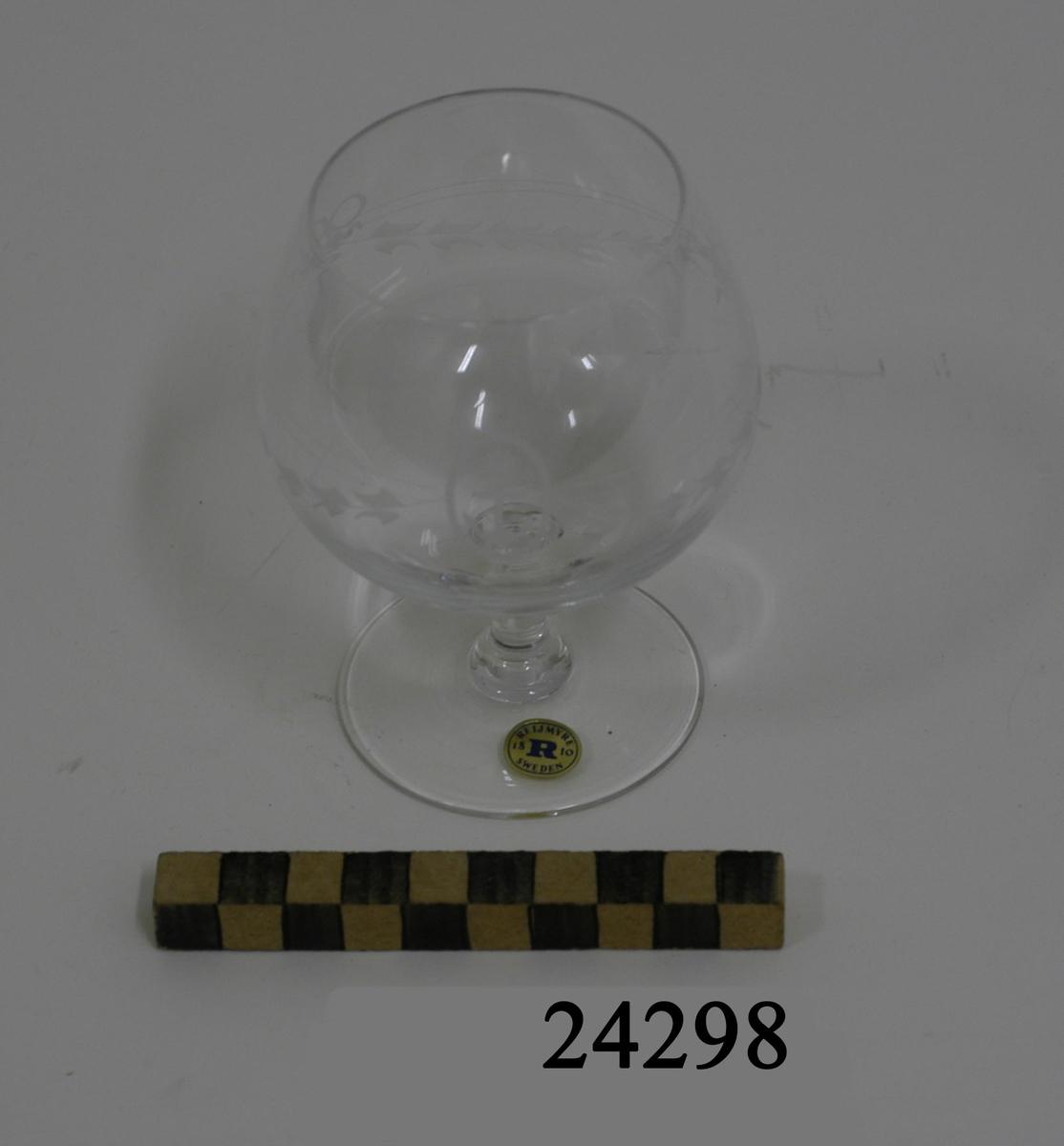 """Handblåst konjakskupa bestående av välvd kupa, runt kort ben och rund, plan fot. Kupan är försedd med slipning: två tunna paralella linjer samt tre nedåtgående bågar med stiliserade blad och två stycken rosetter, samt etsad dekor: Ett krönt stockankare omgivet av tågvirkeslinga. På foten en rund guldfärgad etikett med blå text: """" REIJMYRE SWEDEN 18 R 10 """". Glaset förvaras i blå kartong av papp med vit text: REIJMYRE SWEDEN HANDMADE CRYSTAL, REIJMYRE SWEDEN 18 R 10 """"."""