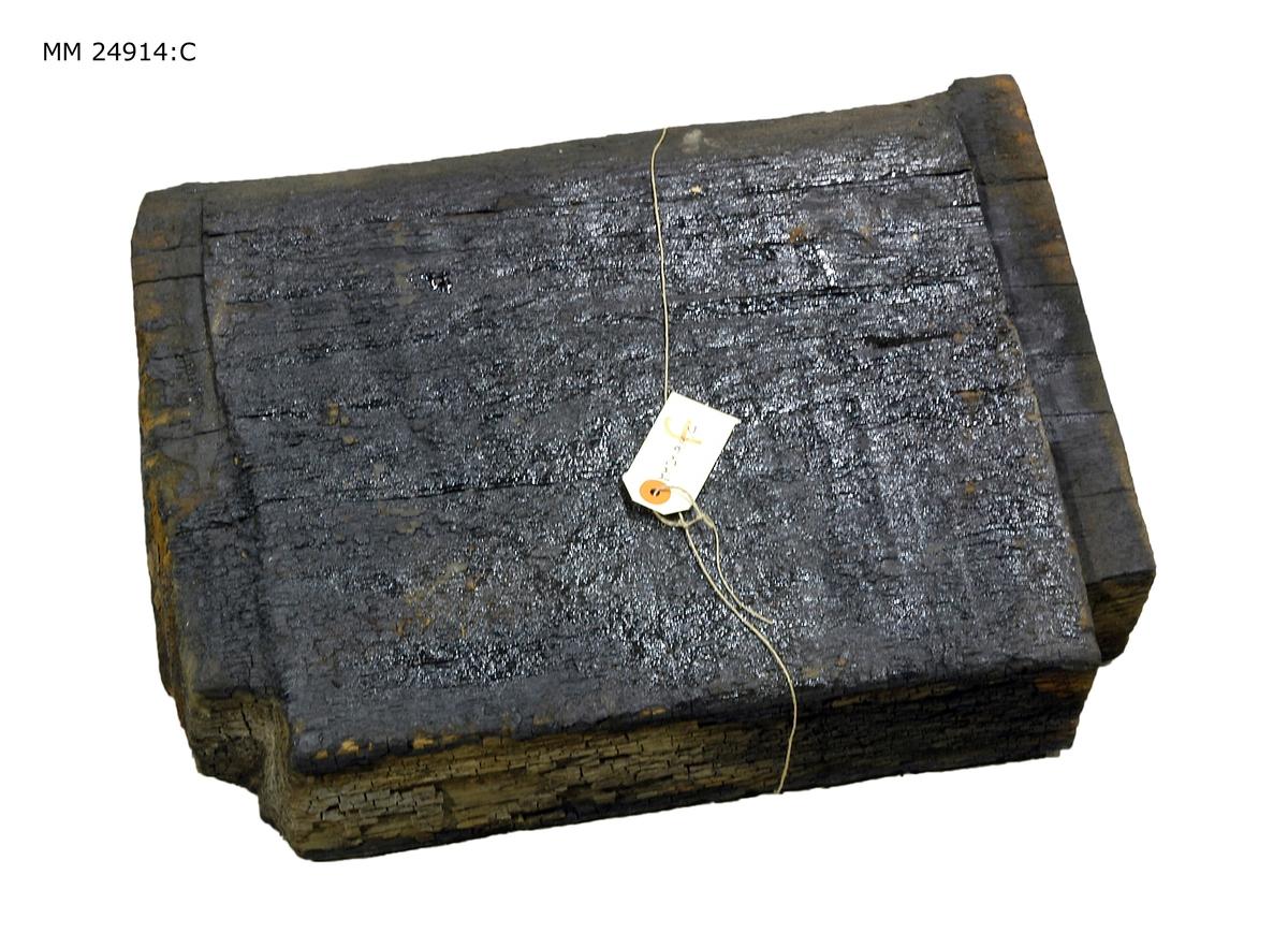 Fyrkantigt trästycke i svartnat trä. Avfasning på tre av kanterna.