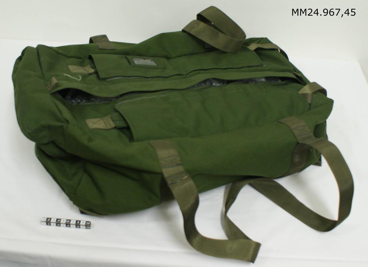 Grön väska av bagmodell. Kan med hjälp av bärremmar som fälls in bakom tygflärpar bäras på ryggen. På ena kortsidan finns en ficka som stängs med dragkedja. Längs hela väskans ovansida sitter en dragkedja för att stänga väskan.