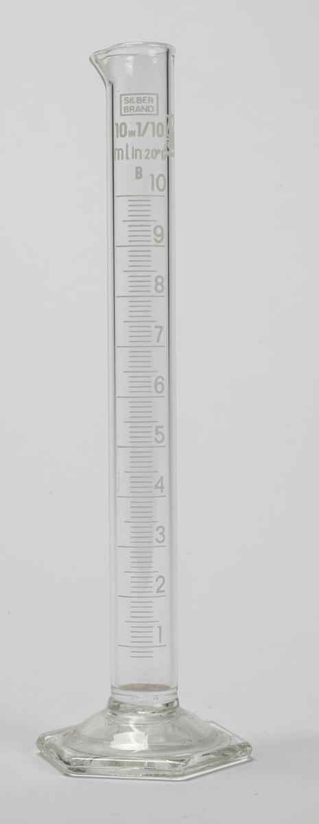 Sylinder i glass som er åpen øverst, har måleskala på siden og sekskantet fot.