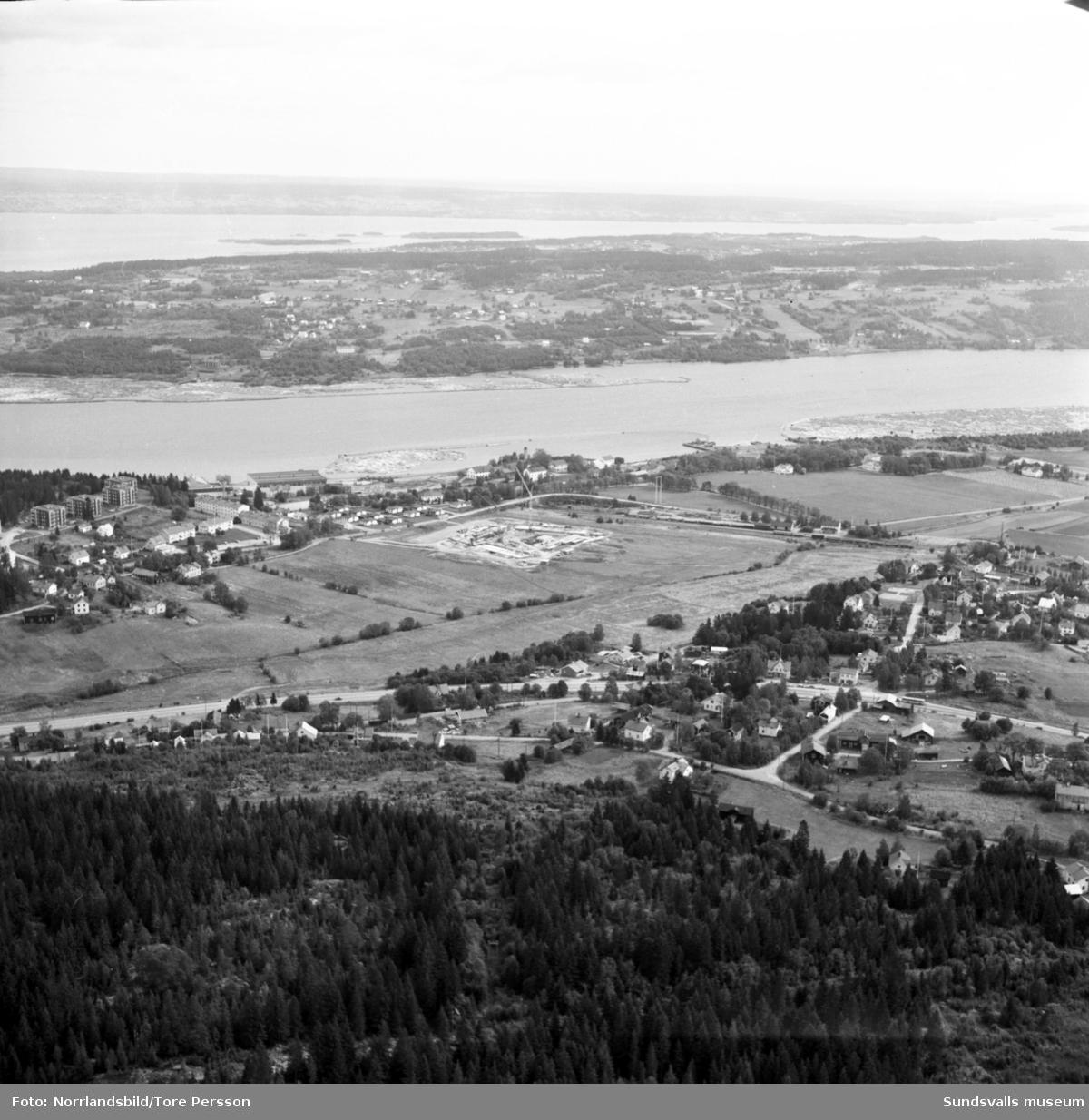 Flygfoton över Finstadalen. I första bildens mitt syns påbörjade markarbeten för nya flerfamiljshus och till höger om det ligger Sundsbruks järnvägsstation