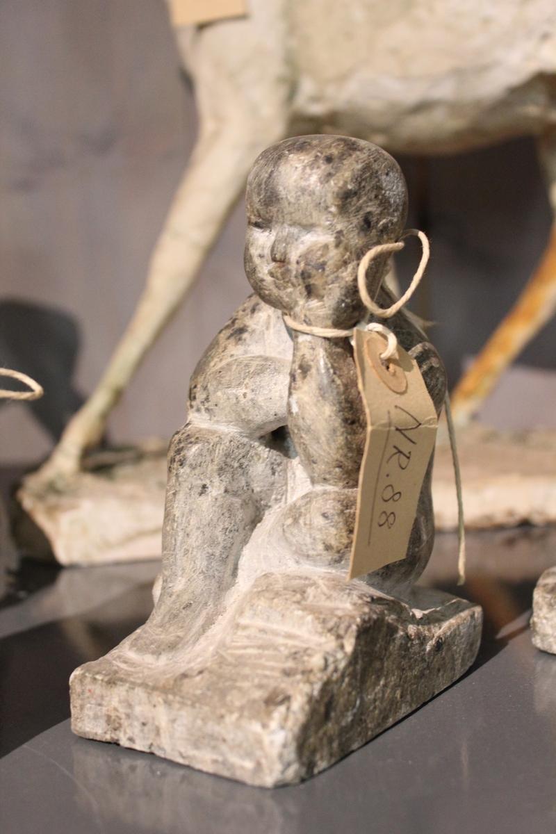 Skulptur i klaberstein av en tankefull gutt. Se også nr.089