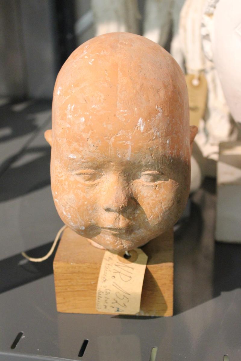 Portretthode i terrakotta av et barn. På sokkel i tre.