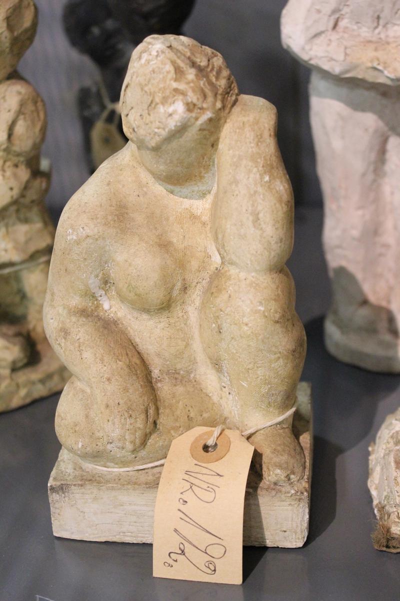 Skulptur i gips av en sittende kvinne.