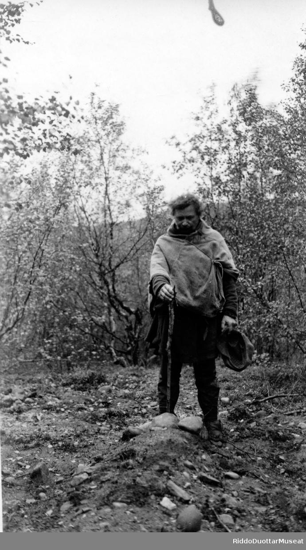 Dievdu cuccoda hávddi luhtte. Mann stående ved en grav.