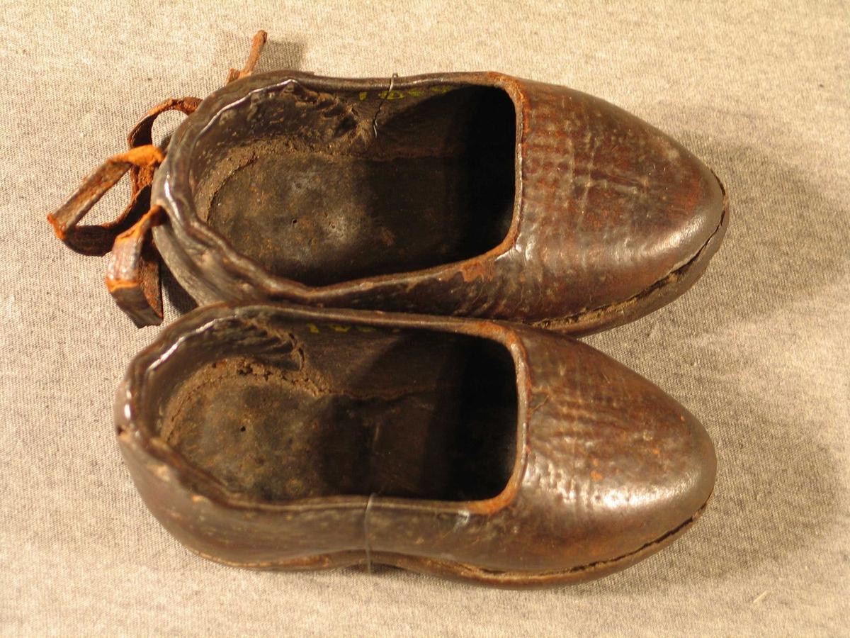 Sydde sko med hardt overlær. På den eine er det festa to lærband på hælkappa, dei an anten knytast om ankelen eller i sløyfe bak. På den andre skoen er desse vekke.