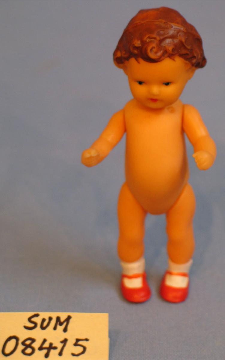 Form: naken dokke med påmalt brunt hår, kvite sokkar og raude sko