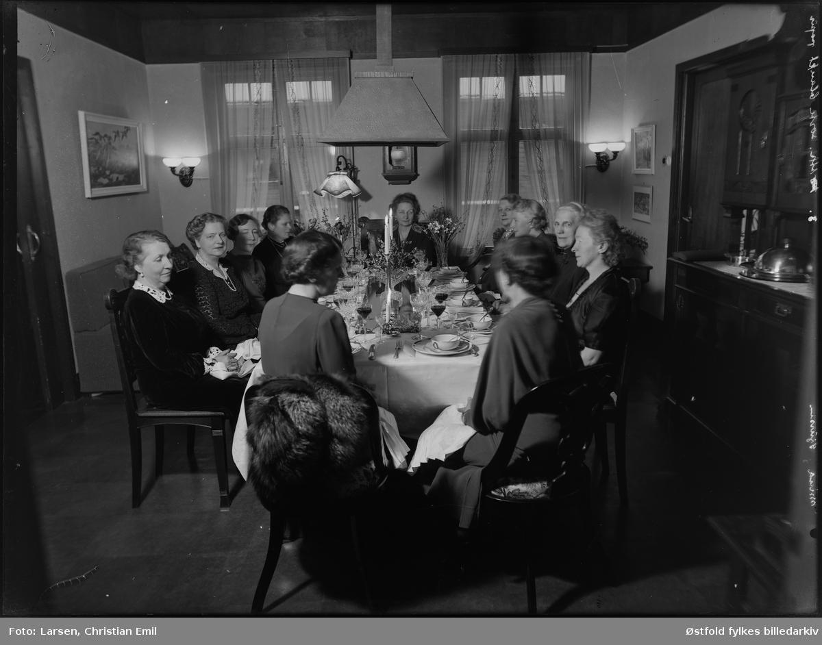 Kvinner festkledd rundt dekket bord til festmiddag i stue. Ukjent sted og personer. Negativ merket Mina Sjursen.