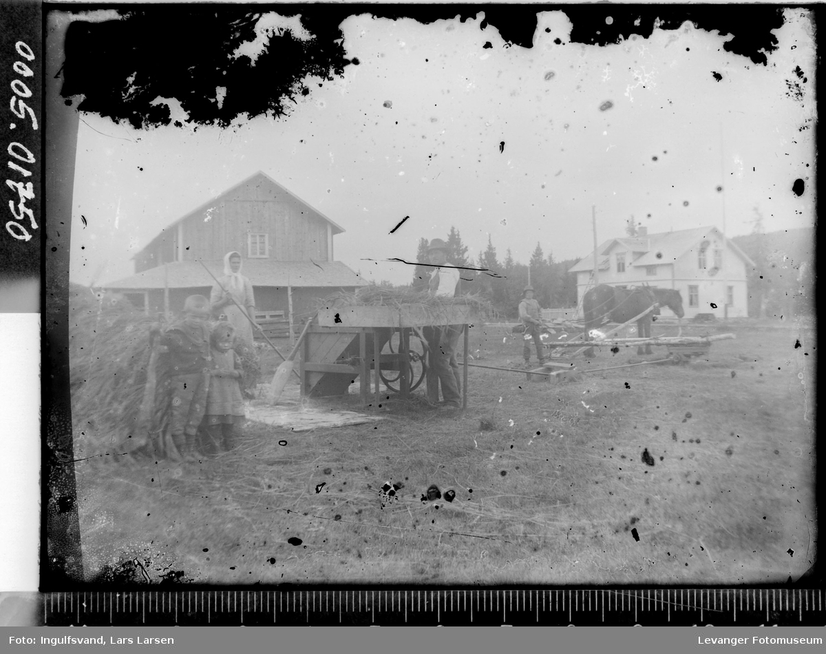 Tre voksne og to barn med hestevandring og hakkelsesmaskin på et gårdstun.