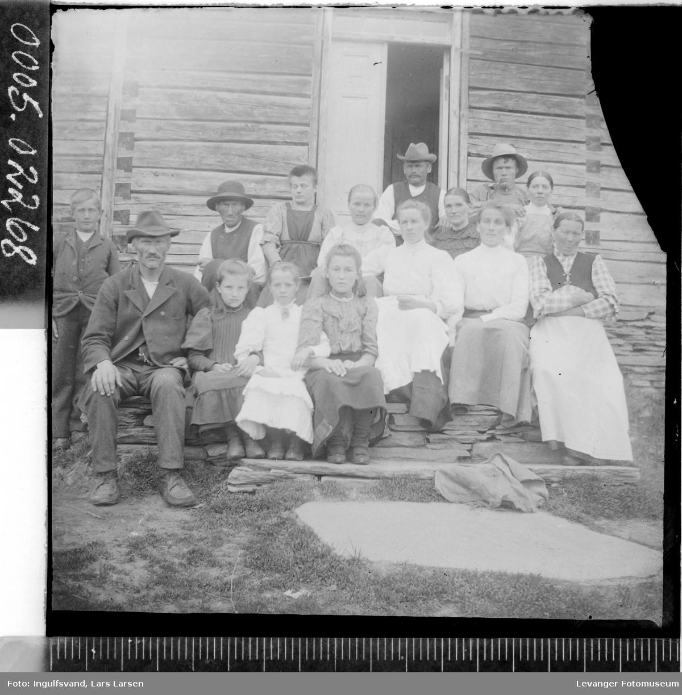 Gruppebilde av fire menn, syv kvinner og fire barn ved et inngangsparti.
