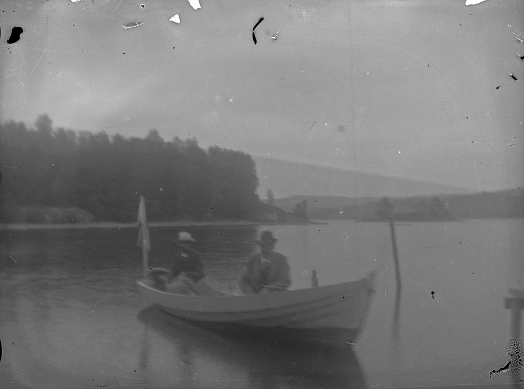 """Text till bilden:""""Två män i en liten båt""""."""