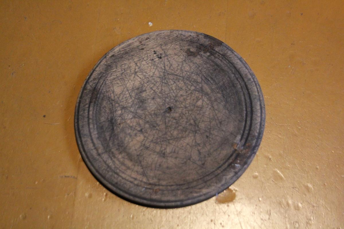 Sirkulær, flat tallereken i tre. T skåret inn i overflaten.