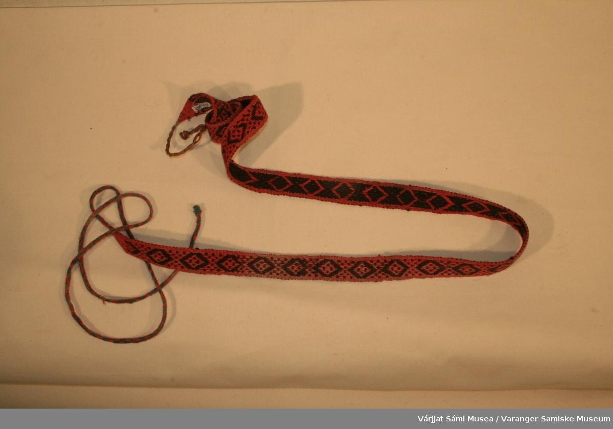 Et grindvevd dameskallebånd, av sort/brunt og rødt ullgarn. Avvikende mønsterelement i enden av båndet. Kort skinnreim i den ene enden, til å feste båndet i fottøyet, lang flette av grønt og rødt ullgarn, til å surre rundt leggen, i den andre enden.
