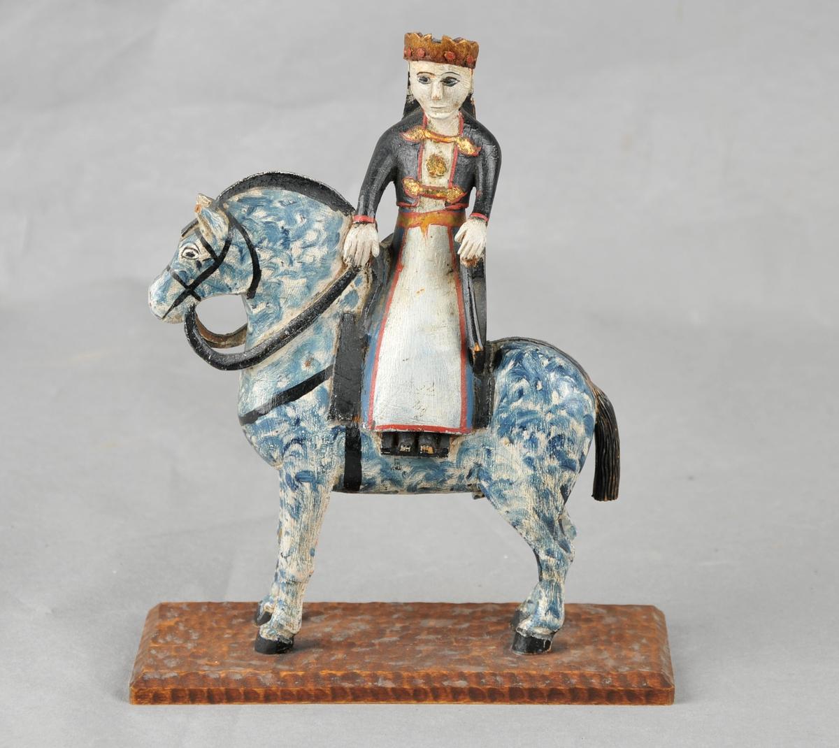Liten skulptur utskoren i tre. Motivet er hest med brur. Brura sit i tverrsal, er pynta med krone på hovudet.  Hesten er kvit med blå spettar. Heile figuren samt sokkelen er måla.