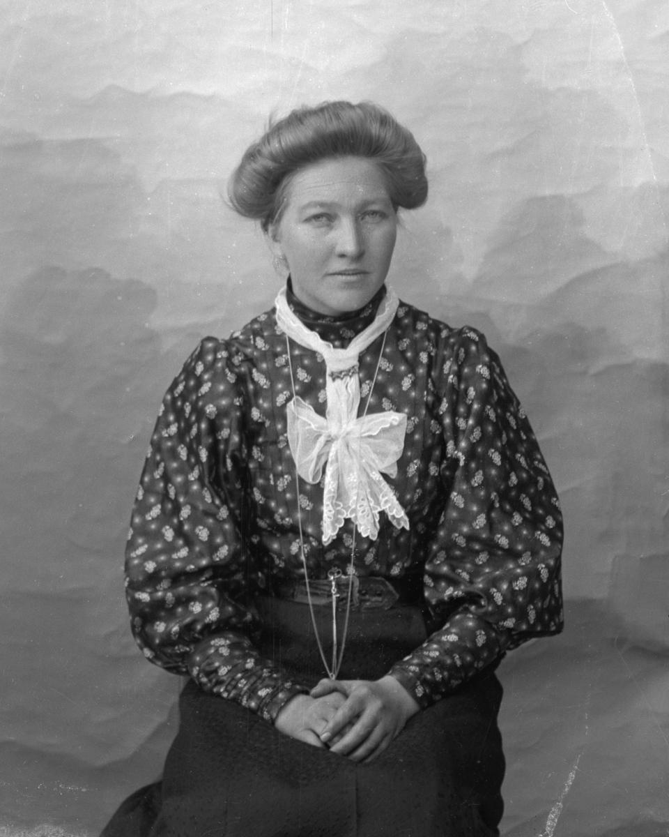 Kvinne sittende foran hvitt lerret, kledd i mønstrete skjorte og mørkt skjørt.
