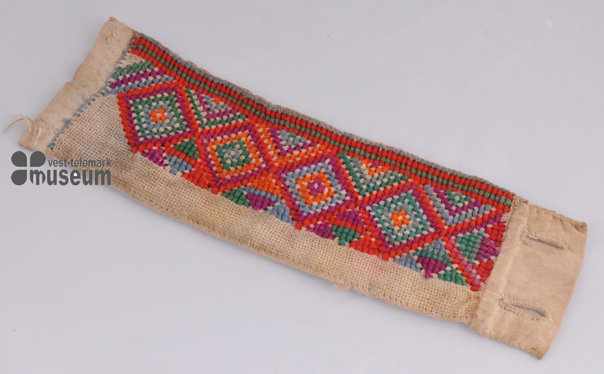 Linning i bomull med broderi i ulltråd på lin. Geometrisk mønster i broderi.To knapphol.