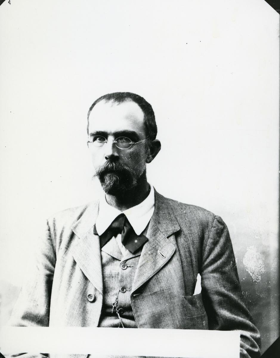 Dresskledd mann med briller, i halvfigur, lerretbakgrunn
