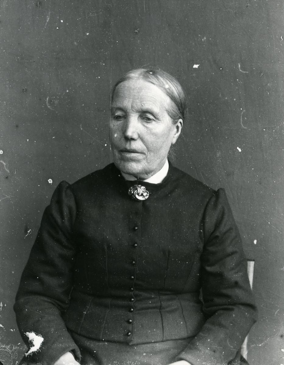 Kvinne i halvfigur, sittende foran lerret