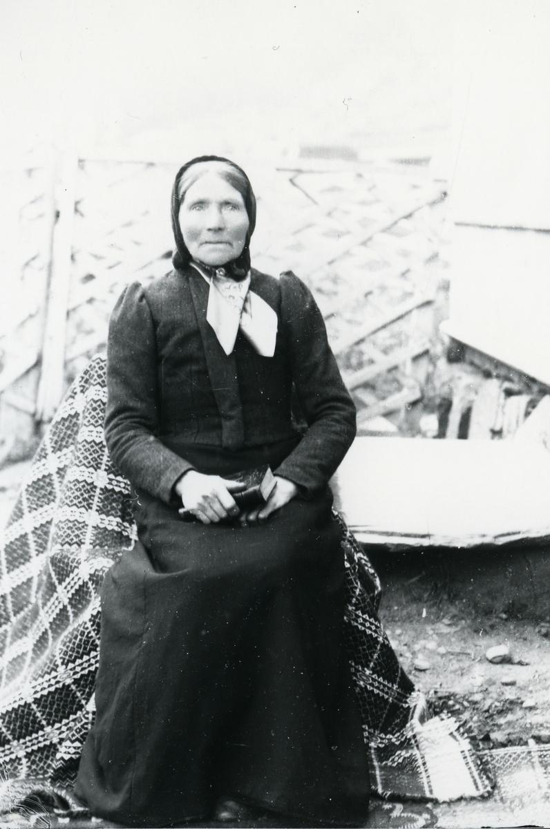 Kvinne med skaut eller lue, med bok (Bibelen?) i fanget, sittende på stol som er tildekket av pledd
