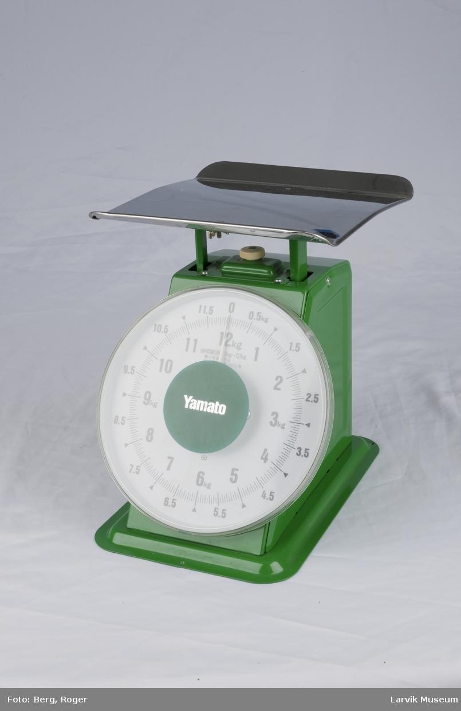 Form: Et brett øverst hvor gjenstanden legges når den skal veies, en stor tallskive (sirkelformet) man kan veie opp til 12 kg. Under brettet er det en knapp å skru på for å stille vekten nøyaktig.