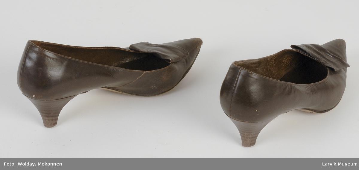 Form: Spiss foran, kort stilletthel, en skinnbit foran som pynt men denne har tydligvis tidligere vært pyntet med en nål eller liknende som har dratt den sammen litt.