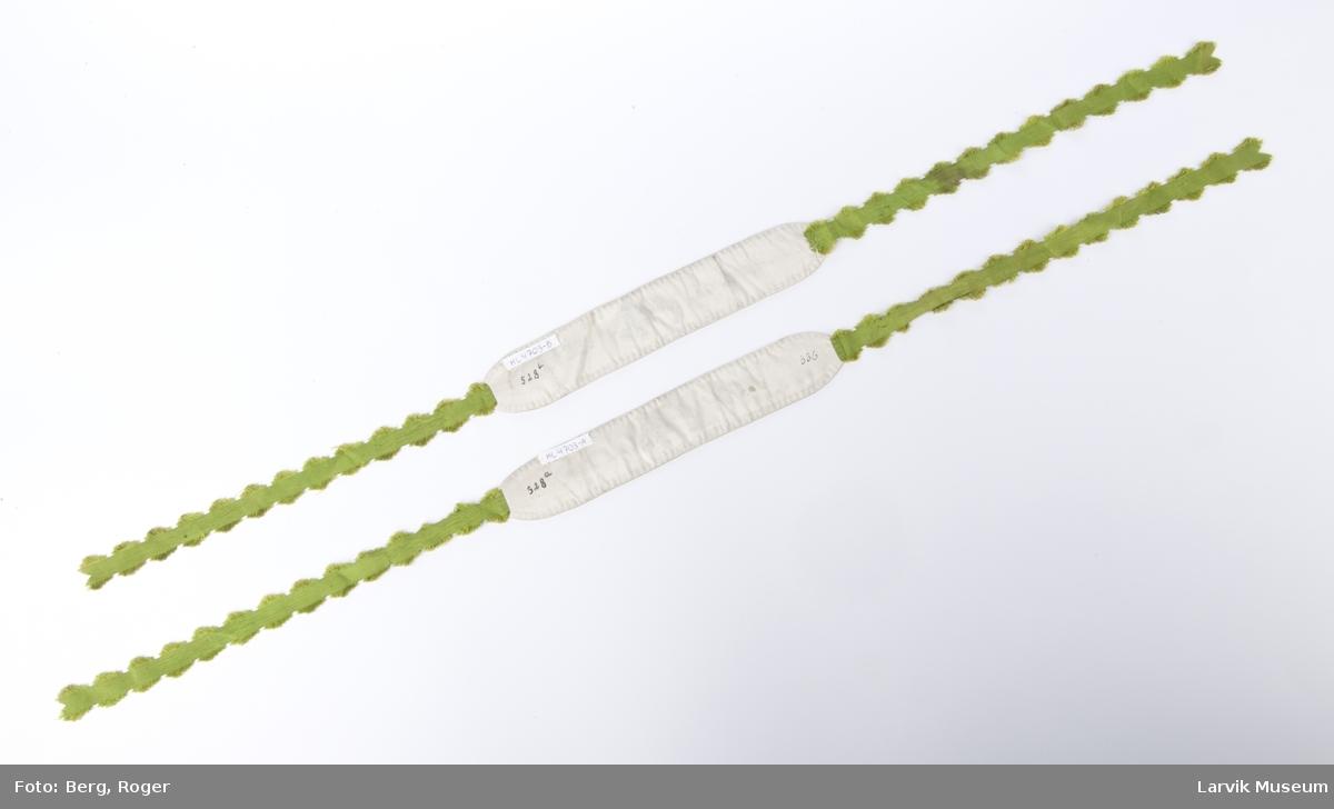 Form: rektangulær, silke med bord langs kanten,  og brodert tekst. I hver ende er et smalere bånd festet.