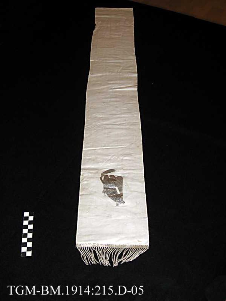 Båndet er hvitt med et sølv-symbol og sølvfrynser.