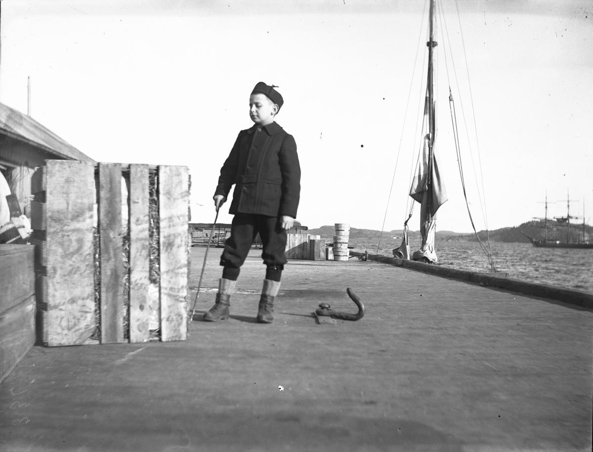 Gutt ved kasse på Dampskipsbrygga i Kragerø