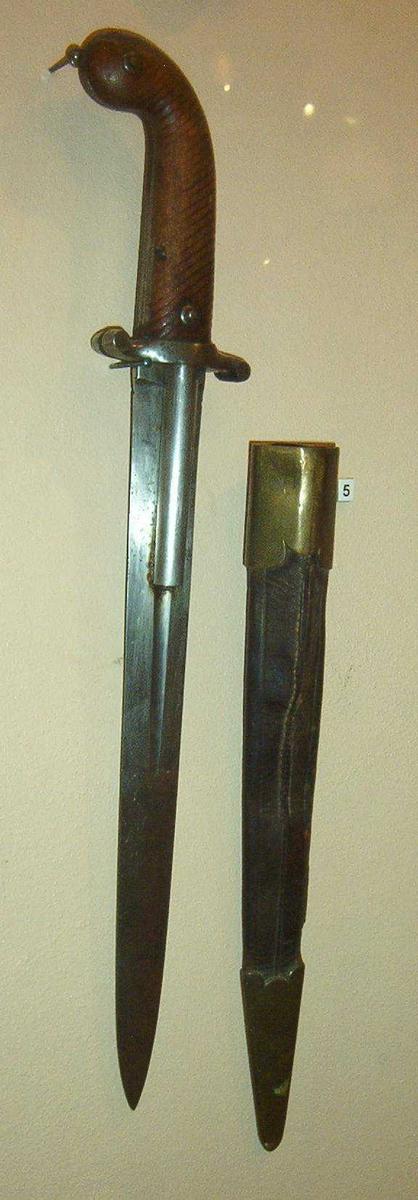 Våpenet har en dobbeltløpet perkusjon bokslåsmekanisme der en dolkeklinge er montert mellom løpene. Dolkeklingen er tveegget med ellipseformet tverrsnitt. Midt på bladets bakerste del finnes to dype blodrender, en på hver side. I disse ligger to glattborede løp delvis nedfelt. Hanene er en integrert del av parerstangen. Kolben er av tre med riflet nettskjæring. Nederst på kolben finnes en ring for fangsnor. Balg medfølger.