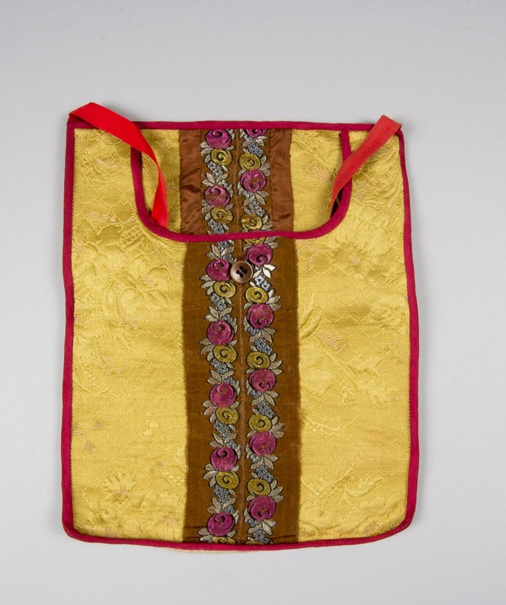 Kjoväska  med u-formad öppning. Av mörkt gult jacquardvävt bomullstyg. Längs mitten två påsydda band med jacquardmönster i glansigt garn: rosenranka i rosa, gult, ljusblått och gråvitt på ljusbrun botten.. Strax under öppningen ett knapphål sytt med brun tråd. Knappen är fyrhålig och ljusbrun. Kantad runtom med mörkrött diagonalvävt konstsilkeband. Framstycket ofodrat, bakstycket av oblekt linnelärft. Midjeband fabriksvävt, av röd bomull.