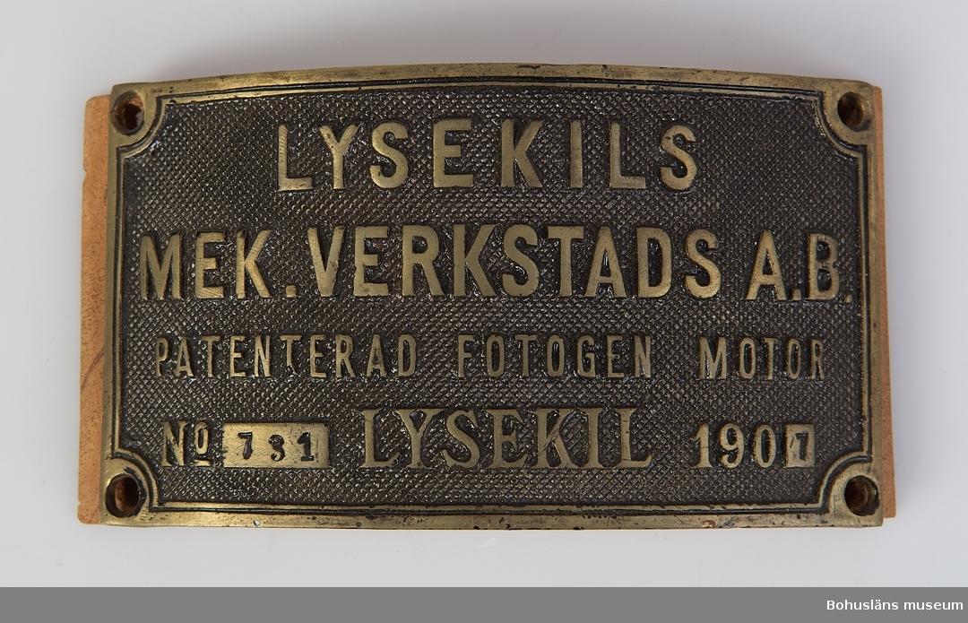 Välvd skylt av kraftig gjuten mässing med skruvhål i varje hörn med i gjutna texten: LYSEKILS MEK. VERKSTAD AB PATENTERAD FOTOGEN MOTOR No 731 LYSEKIL 1901