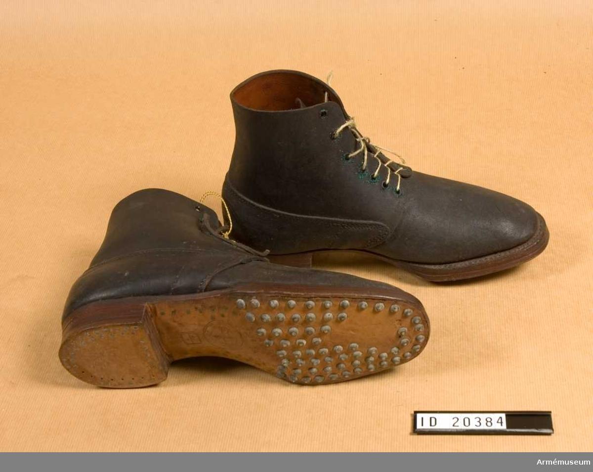 """Snörskor av grovt svart färgat läder med inskärning på framsidan och försedda med sju par järnringar för att snöra skorna med snören av läder. Sulorna är betäckta med järnspikar. På sulorna finns ingraverat en stämpel: """"Durtva""""....... oläslig """"Paris 3.1.13"""". En annan stämpel 27/2. På skons innersida finns stämplar: 1) Stämpel med oläslig påskrift - endast """"1913"""" 2) """"6347"""" med några små stämplar. Pappersetikett med påskriften """"Bekommen den 4 Nov 1913"""". Enligt Kapten W. Granberg."""