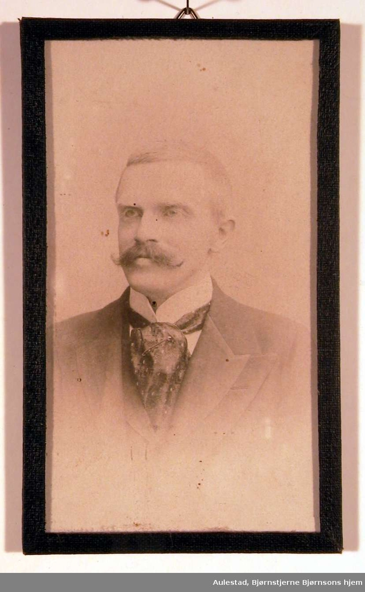 Portrettfotografi av en mann med snurrebart og stort silkesjerf rundt den hvite opprettstående skjortekrave og mørk dress med vest.