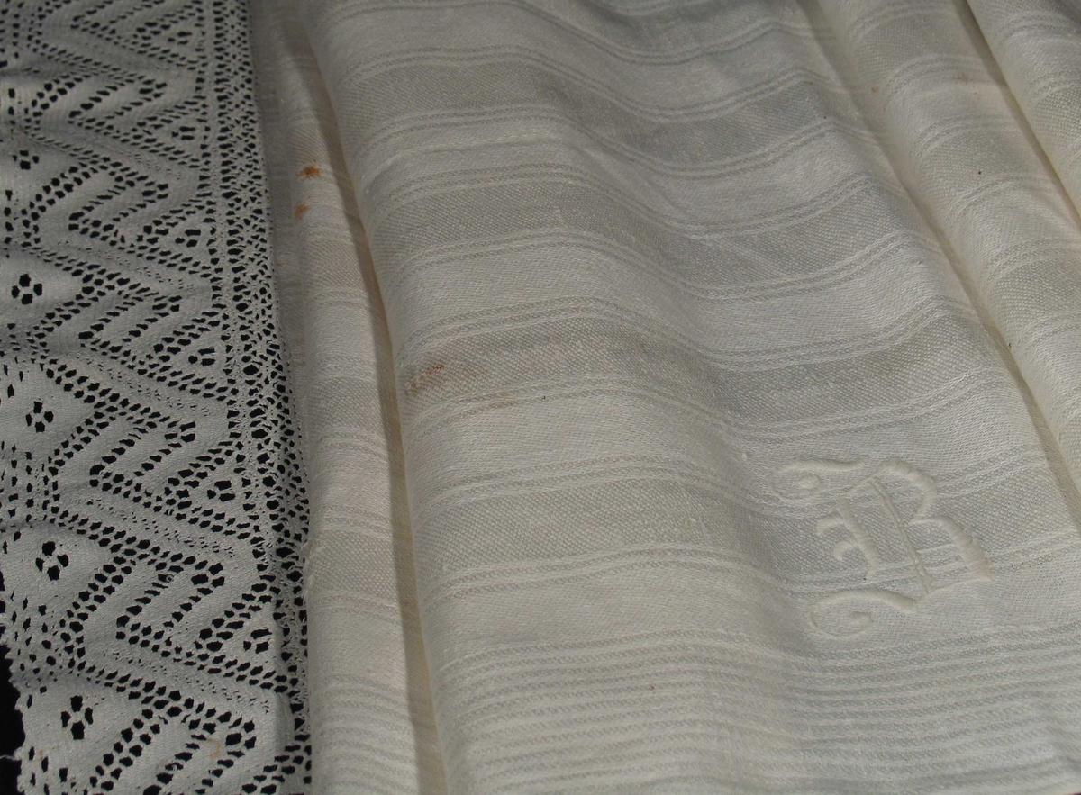 Hvit linløper med langsgående striper og bred heklet blondekant på kortsidene. Brodert monogram med hvit tykksøm.