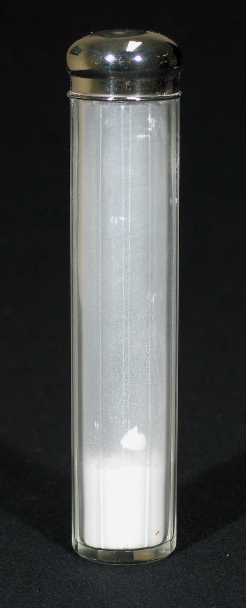 Sylindrisk glassbeholder med sølvfarget kork. Den har slipte kanter og inneholder talkum.