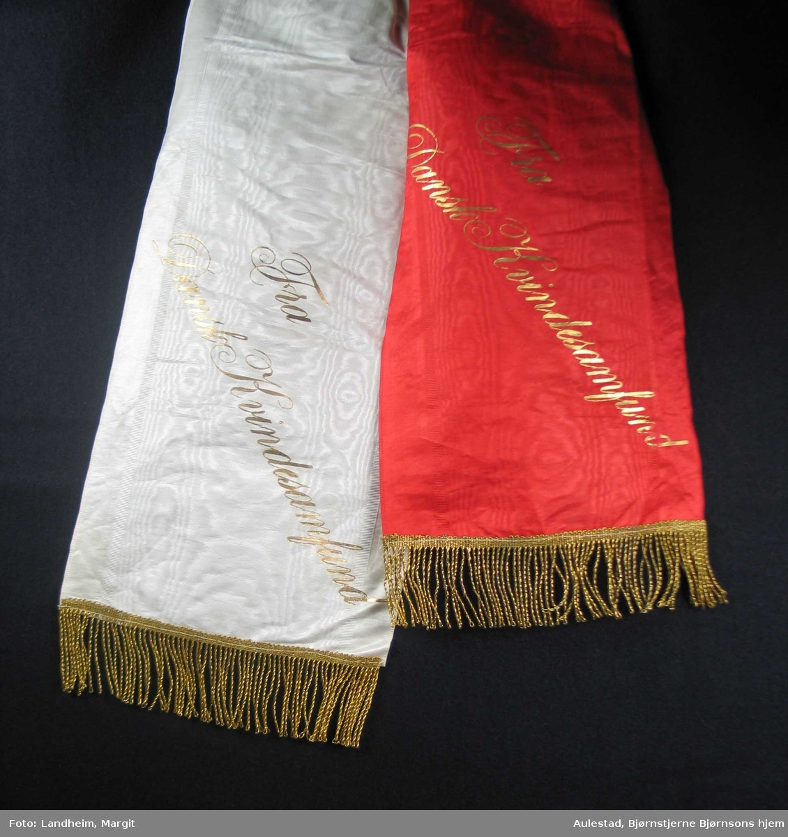 Begravelsessløyfe i rød og hvit silke med frynser og tekst i gull.