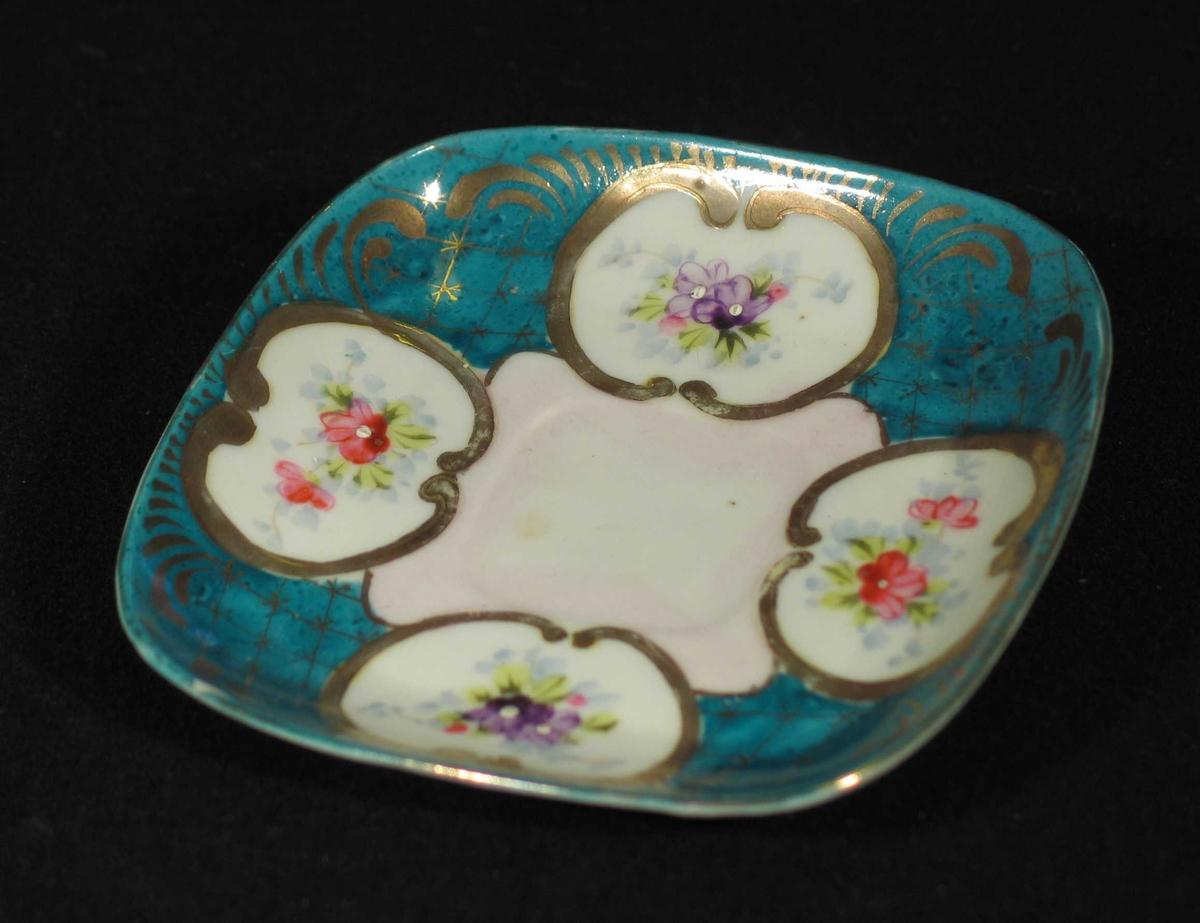 Firkantet skål i porselen med grønn/turkis bunnfarge. Den har fire medaljonger med gull innramming og rosemotiv. Gull rutemønster.