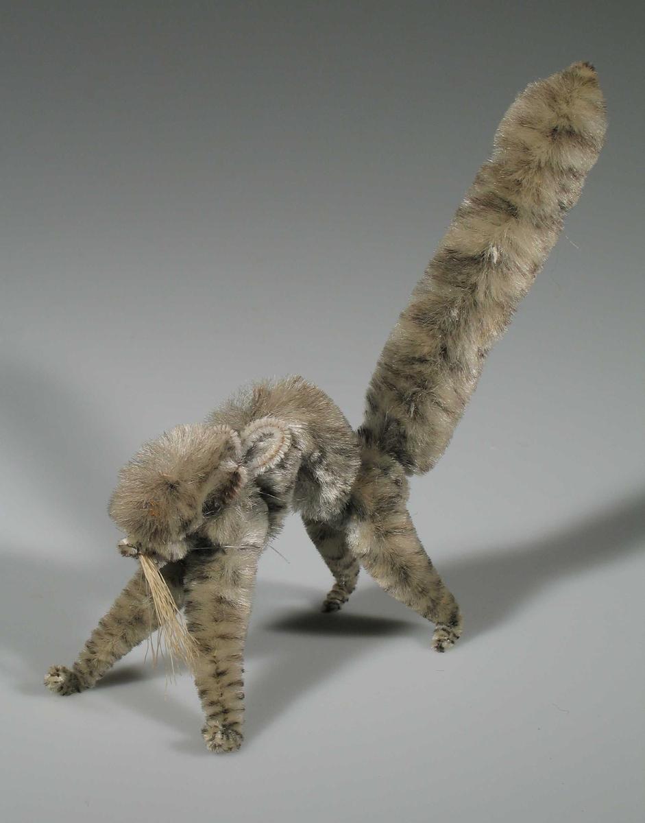 Grå katt skyter rygg, formet av piperenserlignende materiale.