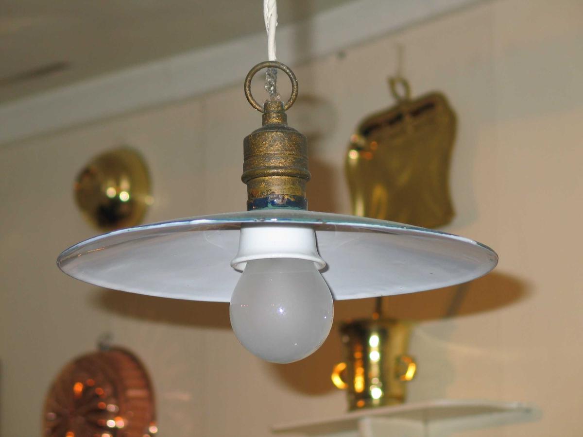 Taklampe med emaljert skålformet skjerm. Den er blågrønn over og hvit under. Sokkelen er trolig i messing. Den har skrue og en ring øverst. Lampen henger i en ledning av eldre dato - ikke i bruk.