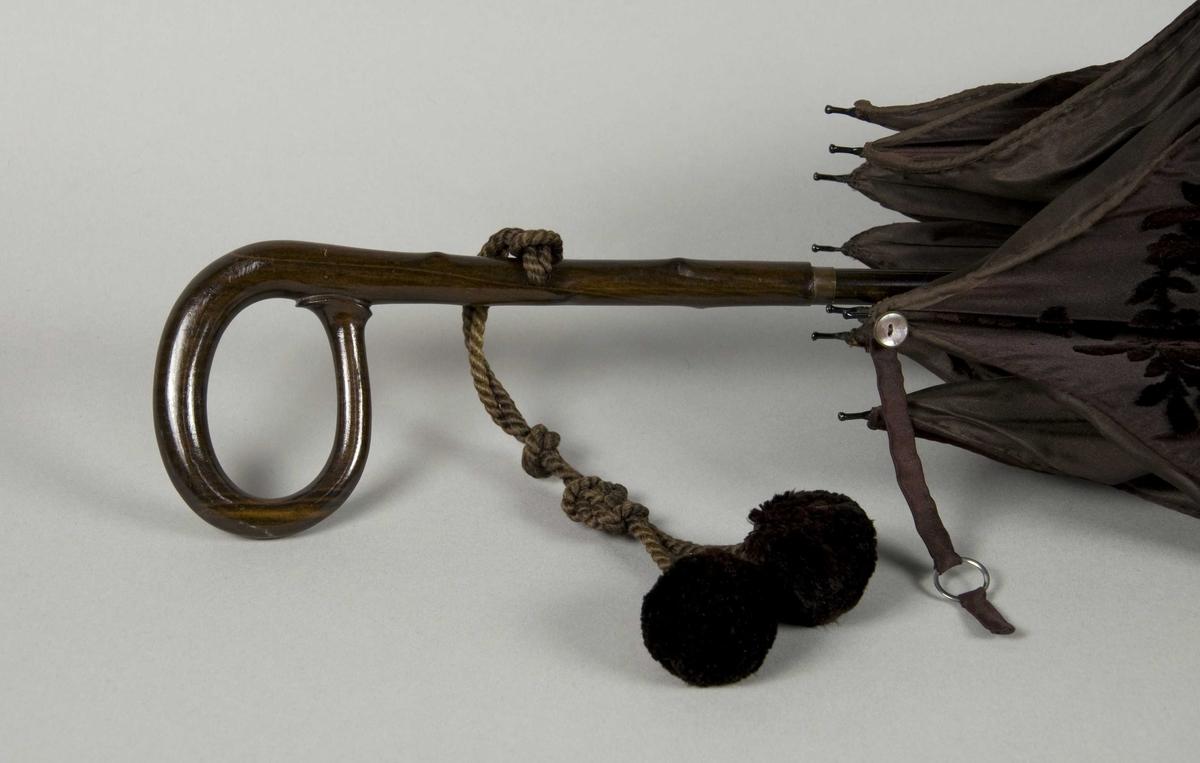 Brun paraply av silke med innvevd blomstermotiv. Stang og håndtak i ett stykke. Metallspiler. Tvunnet brun snor med dusker festet til håndtaket. Fôr av brun silke.