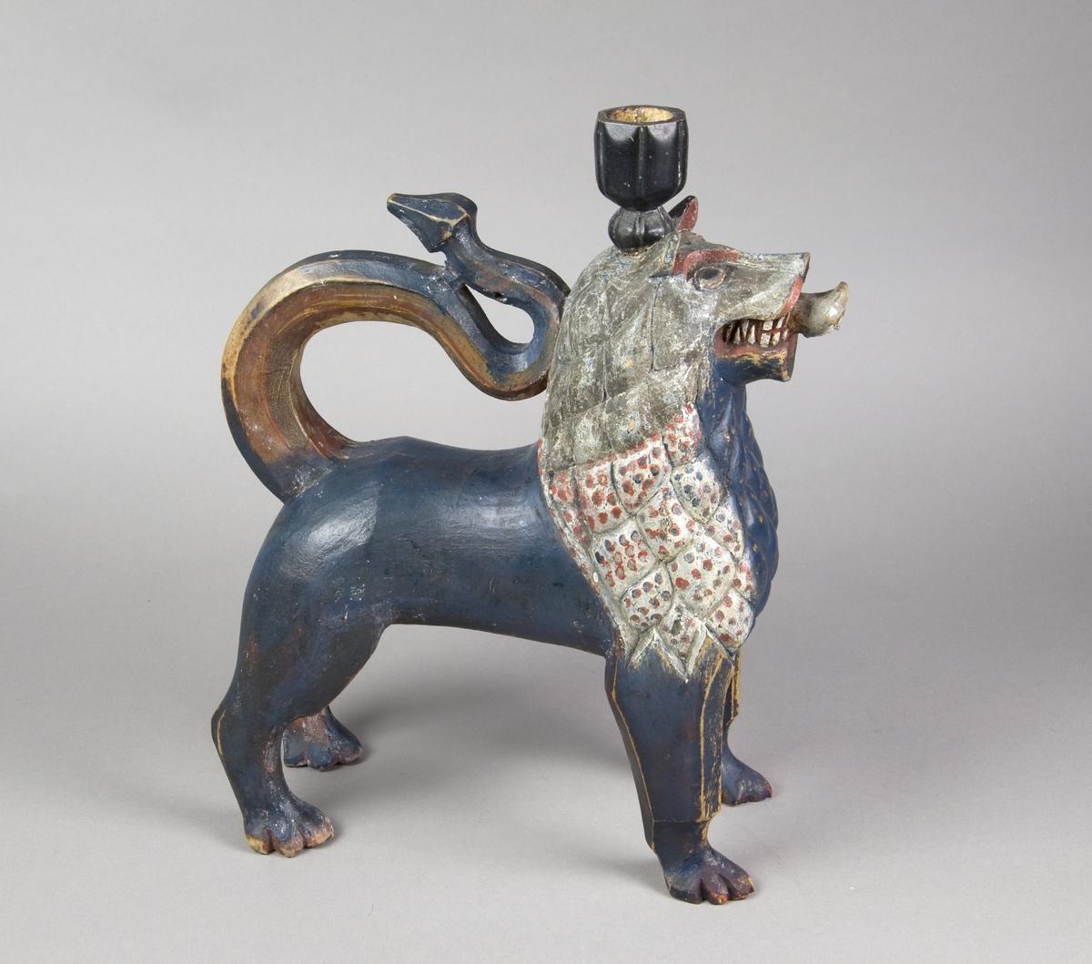 En stående løve med høyreist hode, hvorpå er plassert en lyspipe. Hale i S-formet bue mot løvens nakke.
