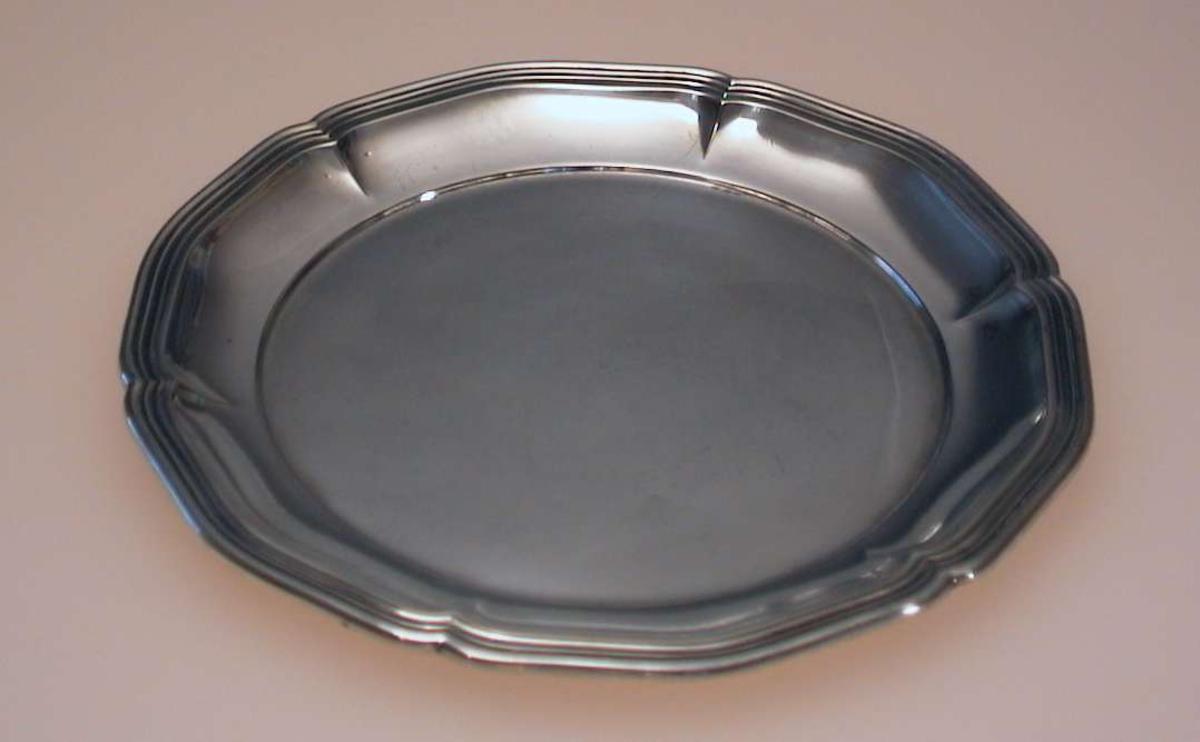 Rund liten tallerken med bølget kant.