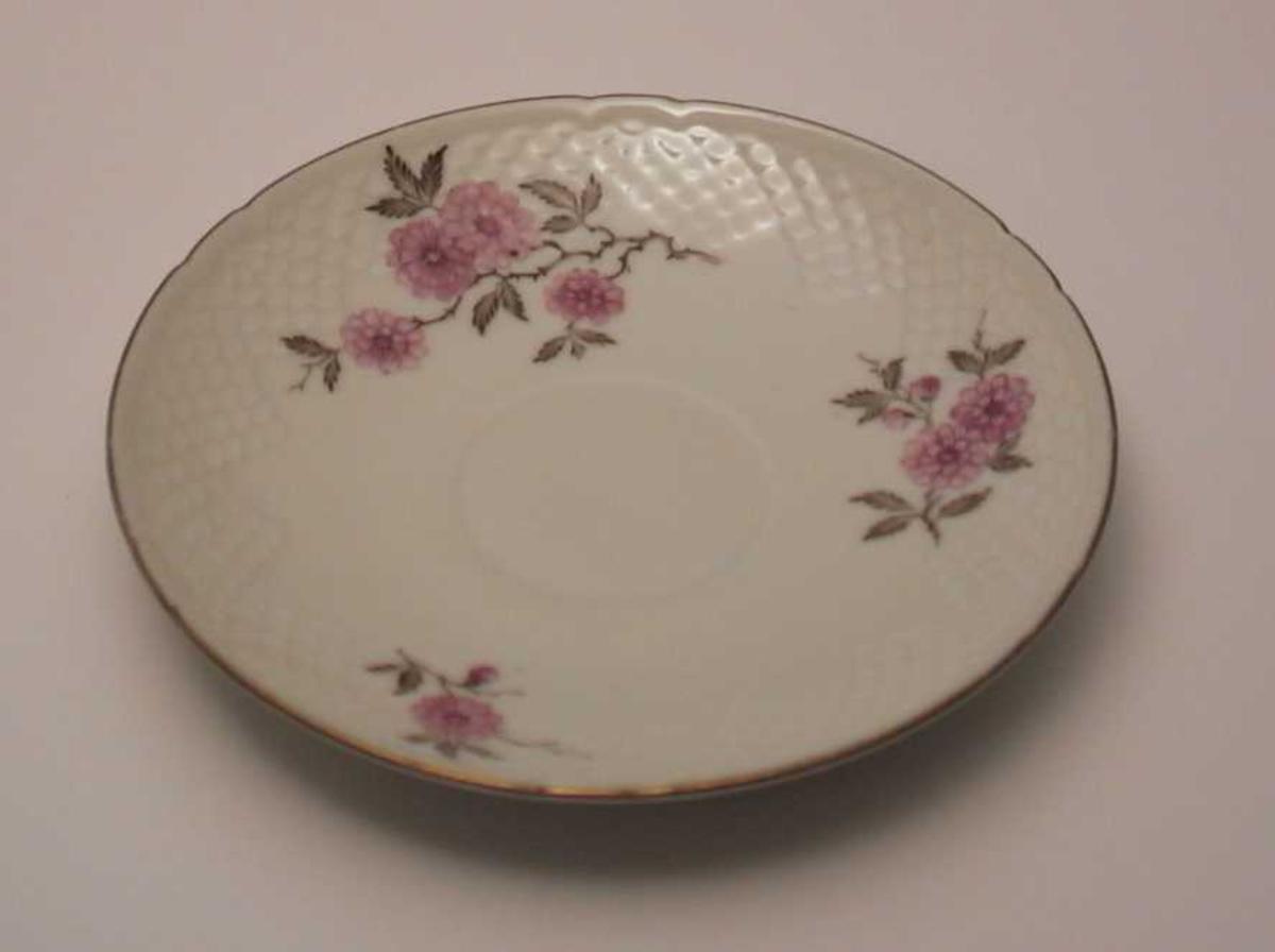 Skål i porselen med blomsterdekor, gullkant og skjellmønster i godset.
