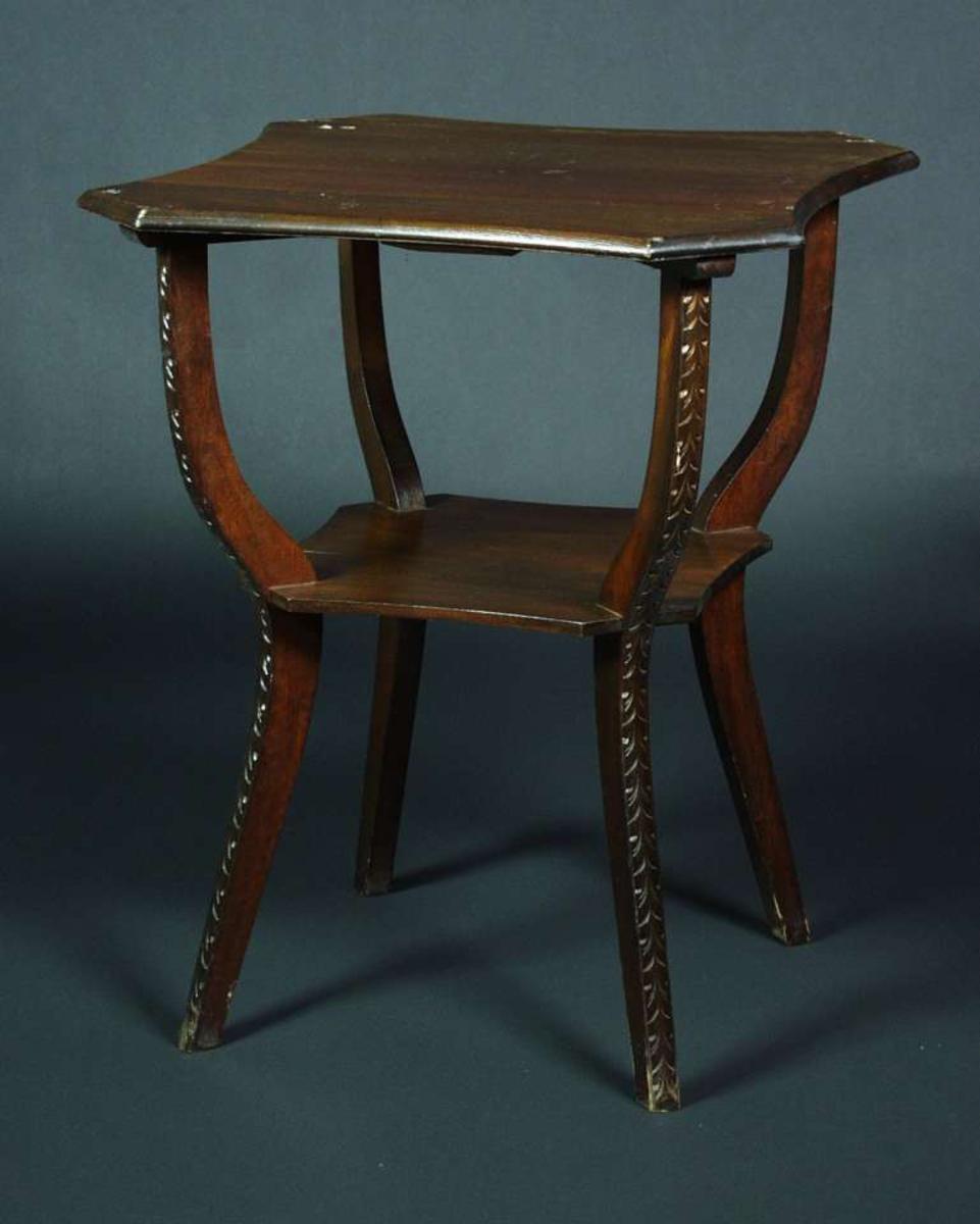 Et lite åttekantet bord i furu og er blitt beistet i brunt. Bordet har en underplate. De fire bena er svunge og har utskjæringer i form av blader.