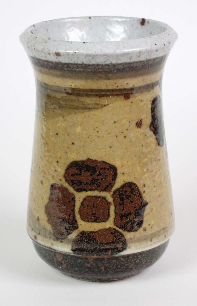 Kraftig beige og brun vase i steingods med saltglasur. Stiliserte blomstermotiv rundt vasen.