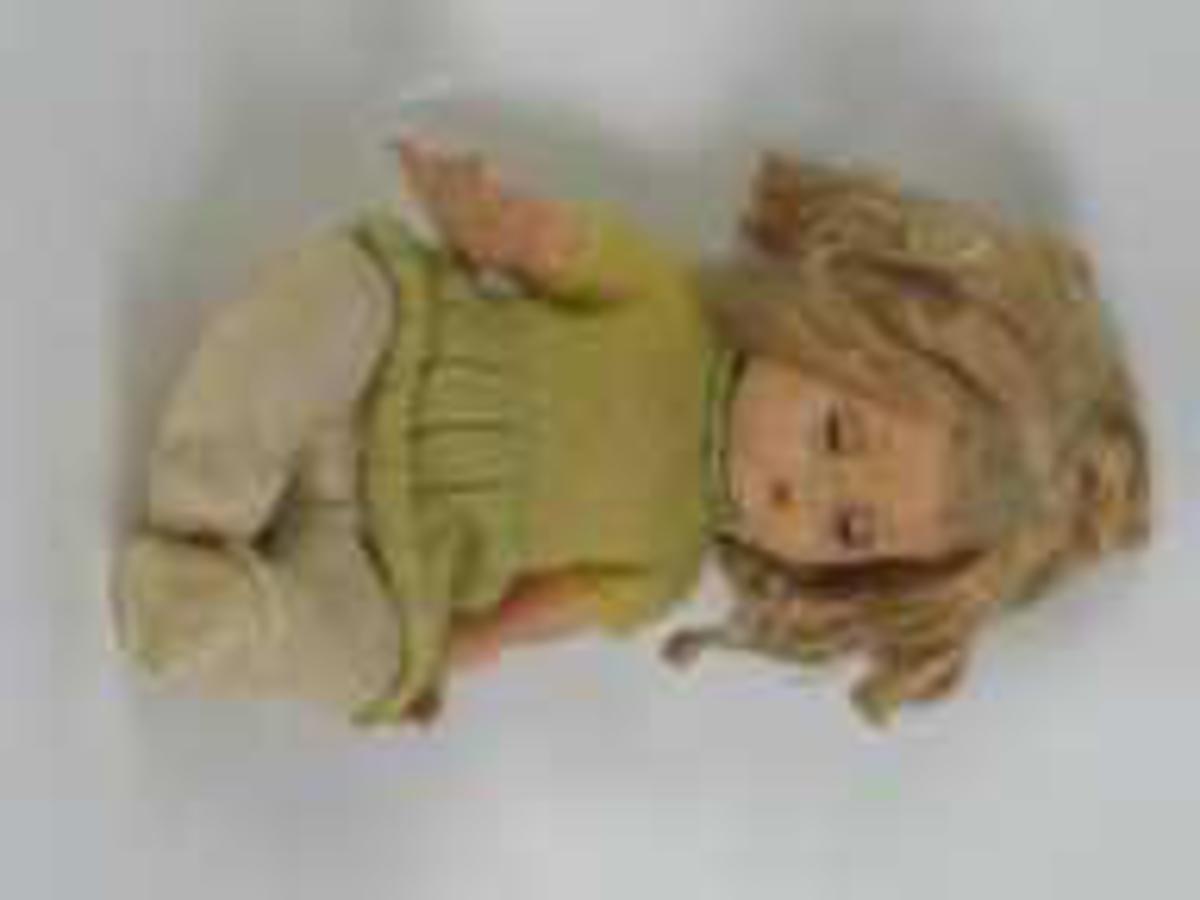Dukken er en sovedukke/babydukke med saran-hår. Klærne er hjemmelaget (strikket kjole og strømpebukse). Materialet er hardplast (cellulose-acetatmateriale).
