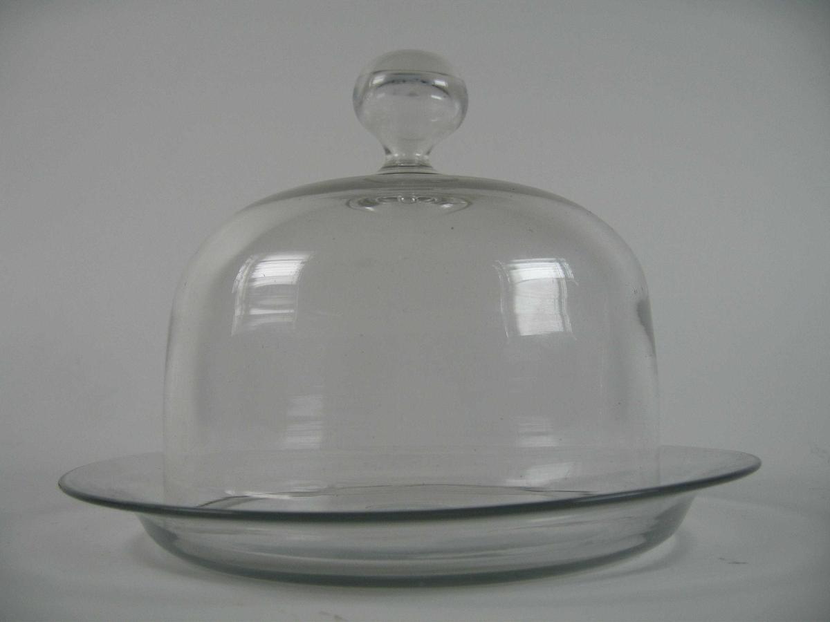Rundt fat med forholdsvis høy kant. Oppi dette står et høyt glasslokk med glassknapp på toppen.